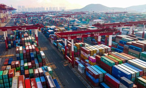 Containers are seen stacked at a port in Qingdao in China's eastern Shandong province on January 14, 2020. - China's trade surplus with the United States narrowed last year as the world's two biggest economies exchanged punitive tariffs in a bruising trade war, official data showed on January 14, on the eve of a deal to ease tensions. (Photo by STR / AFP)